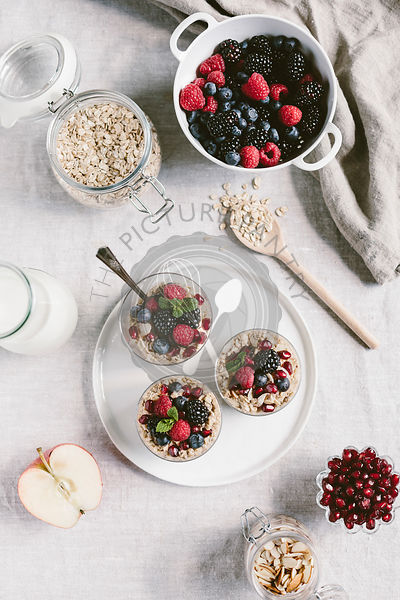 3 clear glasses of apple muesli topped off with berries are photographed from the front view. of apple muesli topped off with berries are photographed from the top view.