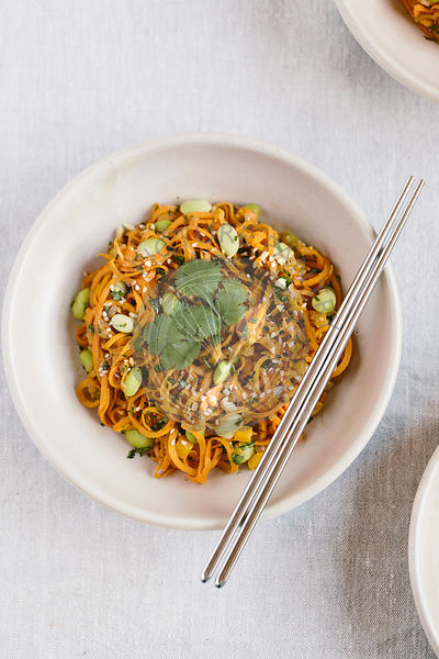 A bowl of sweet potato noodle pad thai is photographed from the top view.
