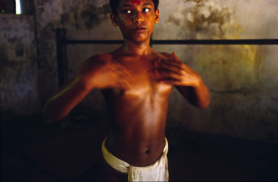 India - Kerala - A boy oils himself before a massage by his teacher