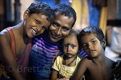 Beautiful family portrait at night on the street in Beniatola, Kolkata, India