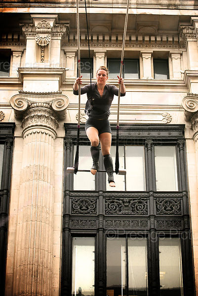 Aerial Performer Standing on Trapeze High above a London Street