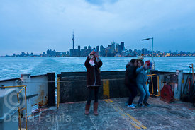 Tourist taking self-portraits from the ferry, with the Toronto skyline on the background
