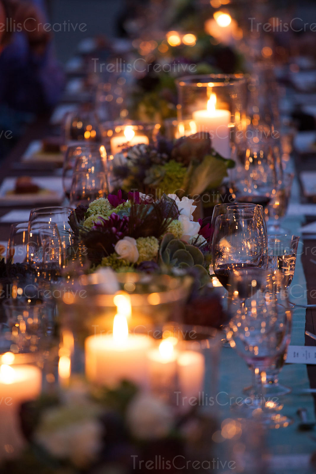 A candlelit dinner table at an elegant party.