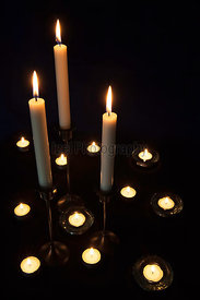 Lit candle and tea lights in holders.
