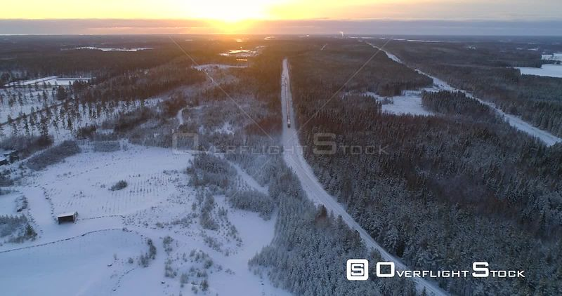 Train in Finnish Winter, Aerial, Reverse, Drone Shot, Following a Cargo Locomotive, in a Snowy Forest, Towards the Scandinavian Wilderness, on a Sunny, Wintry, Evening, in Uusimaa, Finland