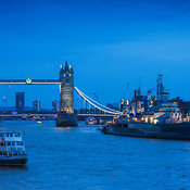 View of the Tower Bridge and boats in the Thames River with lights in the evening, London, England, United Kingdom