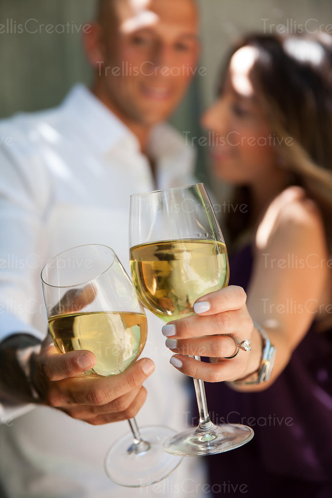 Smiling young couple drinking white wine in the summer