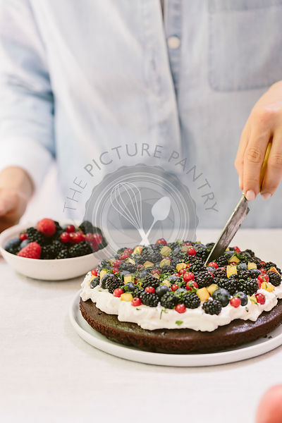 A woman is photographed from the front view as she was slicing a chocolate cake