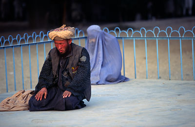 A man prays while his wife sits behind him in a parkAfghanistan - Mazar-i-Shariff - A man prays while his wife sits behind him