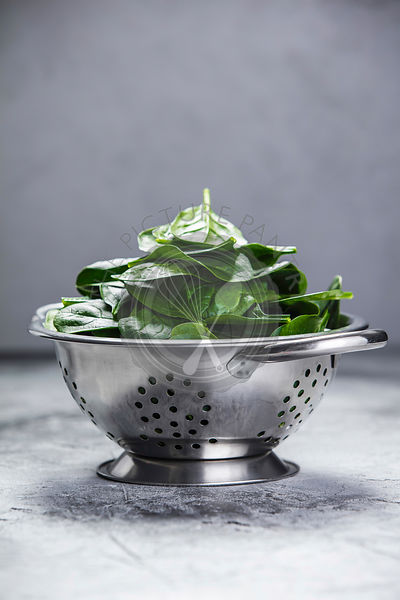 Spinach. Fresh organic spinach leaves in metal colander. Diet, dieting concept. Vegan food, healthy eating. Dark rustic style photo.