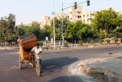 India - New Delhi - A man hauls armchairs on the back of his cycle rickshaw past affluent gated communities in Dwarka
