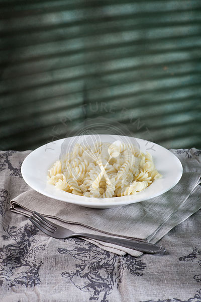 Pasta in the white plate on the table with sunlight shades on the blue background