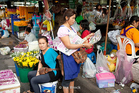 Two women spend their afternoon in the flower market in Bangkok Thailand.