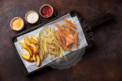 Variety of potatoes for garnish: potato wedges, french fries, sweet potato with three popular sauce for choice on brown background