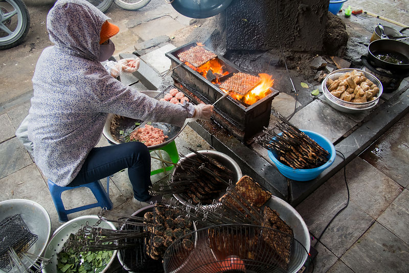 A vendor cooks shrimp and other food over an open flame on the sidewalk in Hanoi, Vietnam