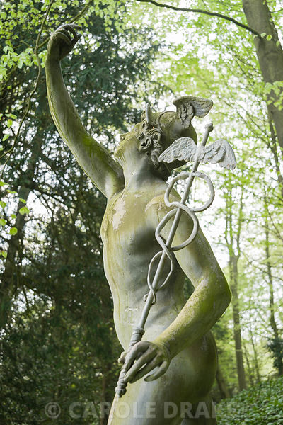 Statue of Mercury sited in a semicircular glade once Charles Bridgeman's turf amphitheatre. Rousham House, Bicester, Oxon, UK