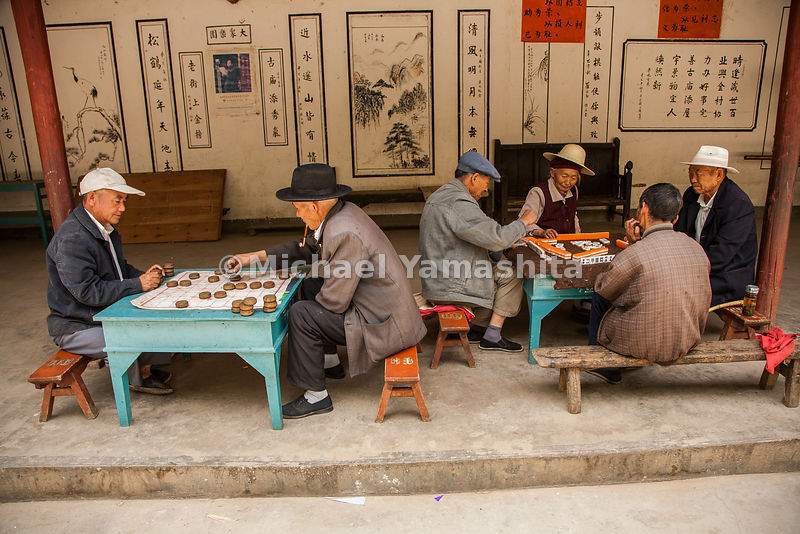 Time for play: Elders in Shaxi's town square are intent upon their board games and Mah Jong tiles.