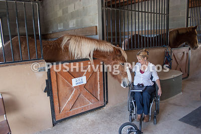Woman in a wheelchair at an adaptive horse riding ranch.