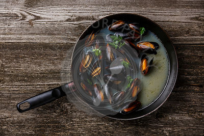 Mussels Clams in cooking pan with parsley on wooden background