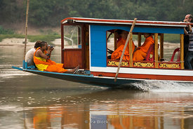 Monks with cameras on a boat on the Mekong River near Luangprabang, Laos