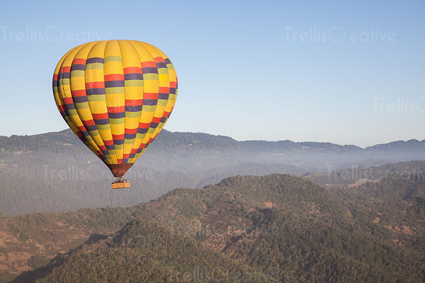 Hot air balloon drifting over a mountain in Napa Valley, California