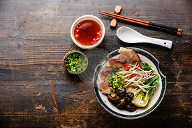 Rice noodles with boiled pork, wheat germ and shiitake mushrooms on wooden background copy space