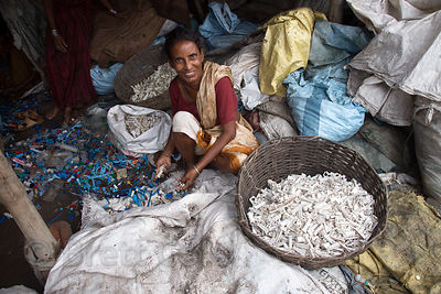 A woman recycles medical waste plastic with no health safeguards, Dhapa, Kolkata, India. Dhapa is a large industrial zone that processes most of Kolkata's garbage and recycling.
