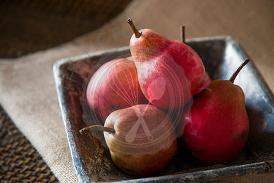 group of red pears in rustic ceramic dish, on sack cloth and woven tray.