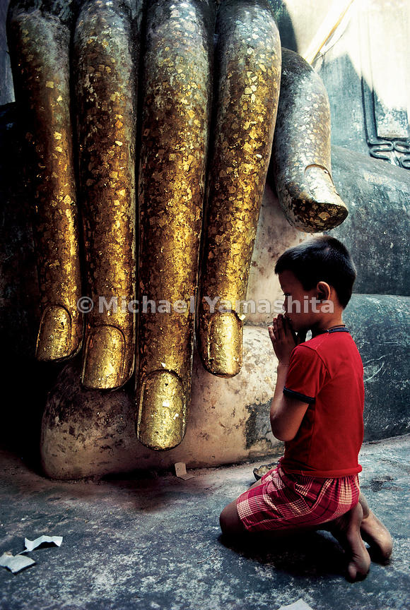The chronicles of Zheng He's voyages as recounted by Ma Huan frequently mention the Thai devotion to Buddha, as well as the large number of temples and monasteries there.  Here a young boy at Si Chom temple is dwarfed by the hand of Buddha, clad in gold leaf.  Ayutthaya, Thailand