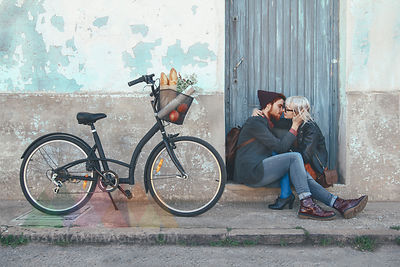 Young couple in love kissing on door step next to a bike