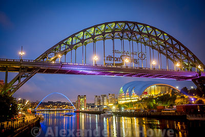 The Tyne Bridge at dusk  with lights from buildings along the banks reflecting in the River Tyne.