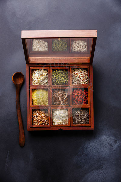 Superfoods and cereals selection in wooden box: oat, mung, quinoa, bulgur, flax seed, goji berry, polba, sesame and chia on dark background