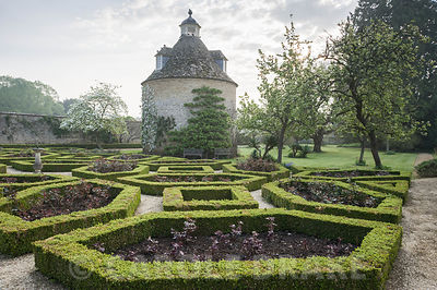 Pigeon House garden with pigeon house, 1685, and box parterre with Cornus nuttallii and new red leaves of hybrid tea roses. Rousham House, Bicester, Oxon, UK