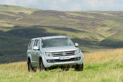 Four wheel drive VW Amarok twin cab pick up driving across upland pasture in North Yorkshire, UK.