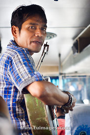 indonesian man busking by singing in the bus