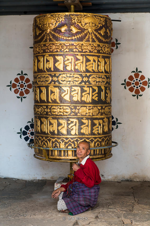 "Large prayer wheel and an old man at the Chimi Lhakhang Monastery or temple, in Punakha District, Bhutan..Built in 1499, the yellow-roofed temple honors Lama Kunley, the ""divine madman""."