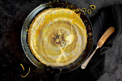 Roasted Cauliflower Citrus Pesto served in a black ceramic bowl. Photographed on a black/grey background.