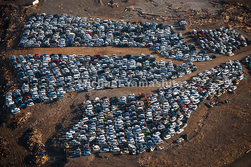 March 11 Great Eastern Japan Earthquake and Tsunami. Measuring 9, biggest ever to hit Japan destroying the NE coast line cities and villages for 200 plus miles. Aerials over Ofunato where cars have been.collected.  Looks like cars were evenly placed showing the japanese sense of order and design.  Cars from every area were piled up neatly.  No one knows where the debris will be taken as there is reported to be 200 million tons of it.