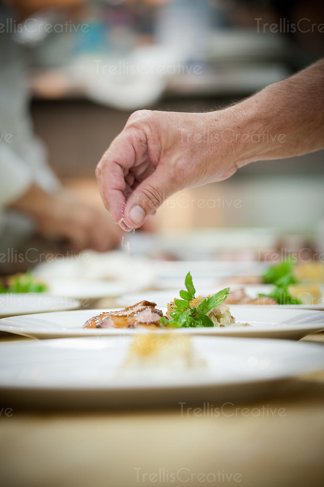 A man's hand sprinkles salt on a plate of meat