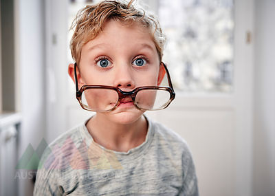Portrait of playful boy with oversized glasses
