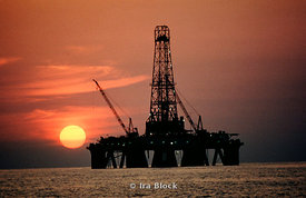Oil rig on Gulf of Mexico, near Texas with sun setting in the background