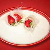 Strawberries splashing in milk