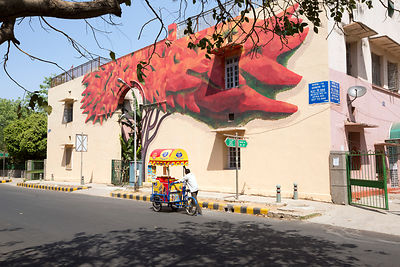 A street vendor passes The Lava Tree by artist Anpu Varkey on display in the Lodhi Colony area of New Delhi