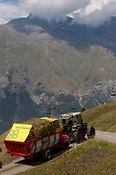 Harvest time in the Alps as a farmer collects grass crop in a forage Wagon
