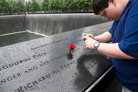 A boy taking a photo of a rose standing in a name on a panel at the South Memorial Pool in 9/11 Memorial Museum, NY.