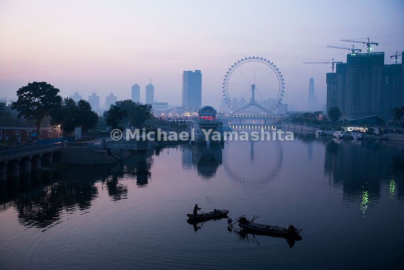 Fishermen work the Hai River in the shadow of the Ferris wheel in Tianjin. The Hai, which flows through Tianjin, fills a stretch of the canal that has been restored to attract tourists.
