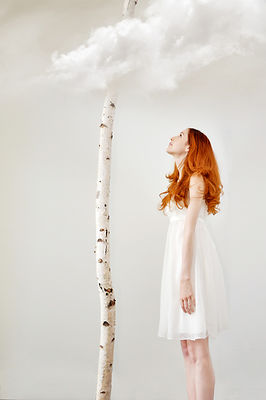 red haired woman looks up at tree and cloud