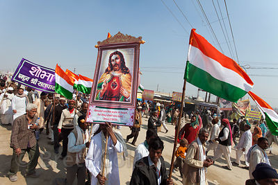 A pilgrim holds a portrait of Jesus in a march at the 2013 Kumbh Mela, Allahabad, India.