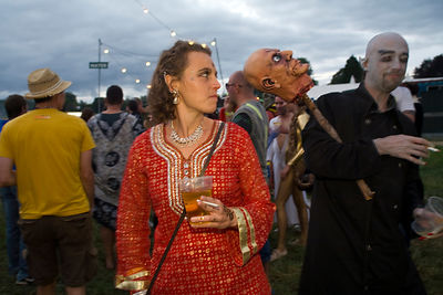 UK - Standon - A woman dances in a field next to a man with a macabre costume at the Standon Calling Festival