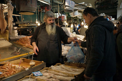 Greece - Athens - A fishmonger serves a customer at his stall in the Athens Central Market on Athinas Street